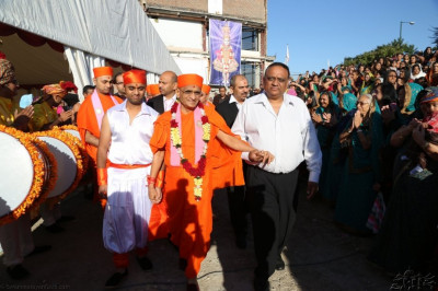Acharya Swamishree is led to the viewing platform by sponsors of the event