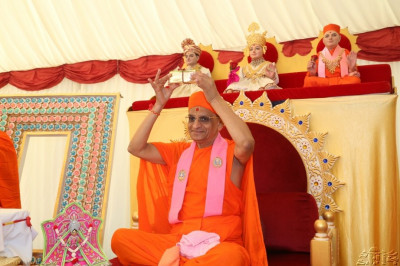 Acharya Swamishree holds up the auspicious brick