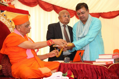 The trustees of Shree Swaminarayan Temple London present a scroll to Acharya Swamishree on behalf of the disciples of London mandal