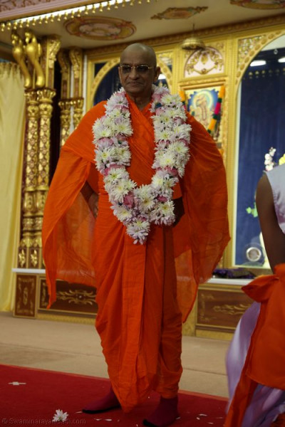 Divine darshan of His Divine Holiness Acharya Swamishree adorned in a garland of fresh fragrant flowers