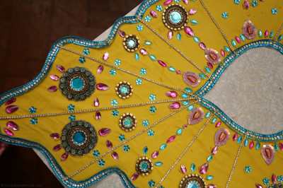 A close up of one of the beautifully decorated 'vagha' made from sandalwood