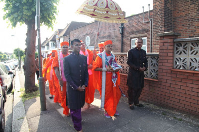 Sants and disciples escort His Divine Holiness Acharya Swamishree into Shree Swaminarayan Temple London