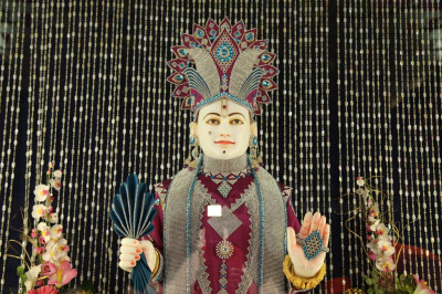 Divine darshan of Lord Shree Swaminarayan adorned in magenta and cyan coloured crystal and diamond garments