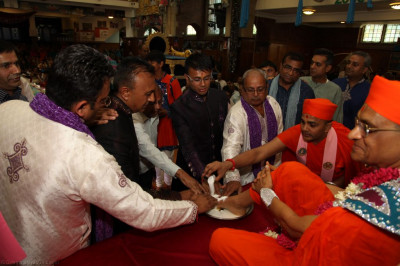 Disciples bathe the divine lotus feet of His Divine Holiness Acharya Swamishree with the five nectars