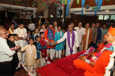 Disciples who have sponsored the evening programme and young disciples who carried gifts offer aarti to His Divine Holiness Acharya Swamishree and Shree Harikrishna Maharaj