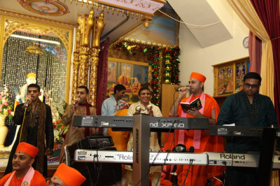 Sants and disciples sing traditional devotional songs accompanied by various instruments