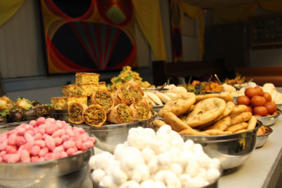 A huge variety of savoury, snack and sweet items are arranged on dishes by disciples ready to be placed into the Annakut