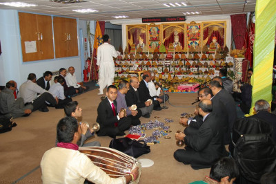 Disciples play traditional indian percussion instruments as aarti is performed