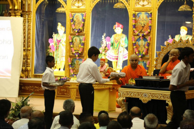 Disciples dressed in white shirts and black trousers present swagat items to His Divine Holiness Acharya Swamishree