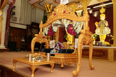 Divine darshan of Shee Harikrishna Maharaj seated on a golden swing dining on a traditional evening meal with Indian sweets