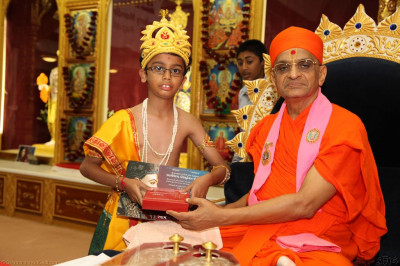 His Divine Holiness Acharya Swamishree presents young disciples with an education award for finishing in the top 3 in Swamibapa Gujarati Classes 2013