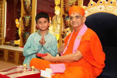 His Divine Holiness Acharya Swamishree presents young disciples with an achievement award for achieving and excelling in musical examinations