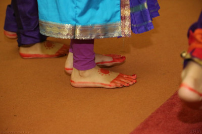 A close up of one of the performers foot covered in traditional indian kumkum patterns