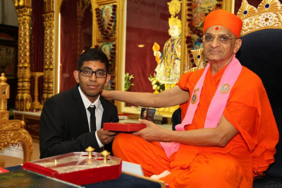 His Divine Holiness Acharya Swamishree presents an Excellence certificate and prasad to all disciples who have achieved outstanding academic results this year