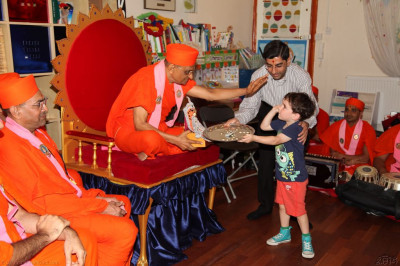 His Divine Holiness Acharya Swamishree blesses the child by giving him a high-five