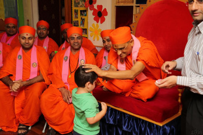 His Divine Holiness Acharya Swamishree presents a chandlo to the children