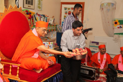 His Divine Holiness Acharya Swamishree presents all with prasad fruit