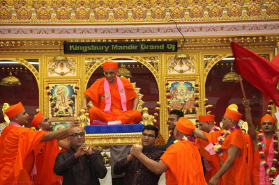 Acharya Swamishree is carried on the palanquin into the sabha