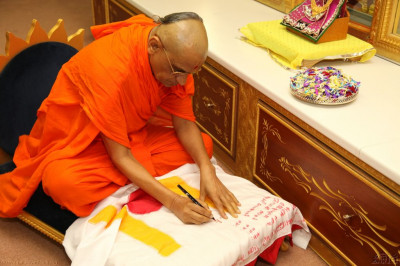 Acharya Swamishree consecrates the new flag of the temple