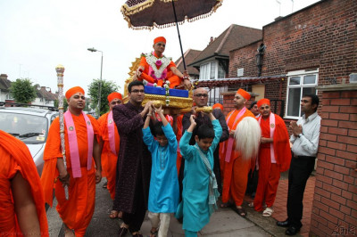 Acharya Swamishree adorned in beautiful fresh flower and crystal garments is carried aloft in a golden palanquin