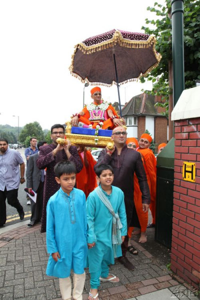 Acharya Swamishree is carried to the front of the temple