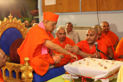 The sacred mahapoojan thread is tied around the right wrist of His Divine Holiness Acharya Swamishree