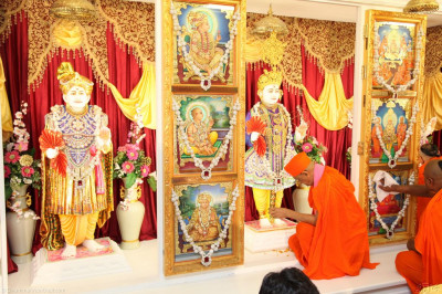 His Divine Holiness Acharya Swamishree applies chandlo to the divine lotus foot of Lord Shree Swaminarayan