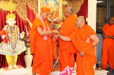Acharya Swamishree ties the sacred red mahapoojan thread around all the right wrists of all Sants present