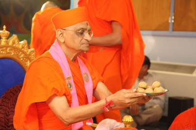 His Divine Holiness Acharya Swamishree offers traditional Indian sweets to the Lord as part of the mahapoojan ceremony