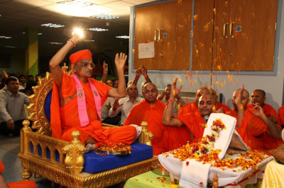 His Divine Holiness Acharya Swamishree showers fresh fragrant flower petals at the lotus feet of Lord Shree Swaminarayanbapa Swamibapa as this part of the ceremony concludes