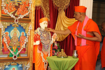 His Divine Holiness Acharya Swamishree offers traditional Indian sweets to Jeevanpran Shree Muktajeevan Swamibapa