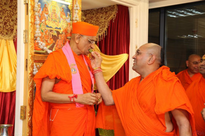 Sants offer traditional Indian sweets to His Divine Holiness Acharya Swamishree
