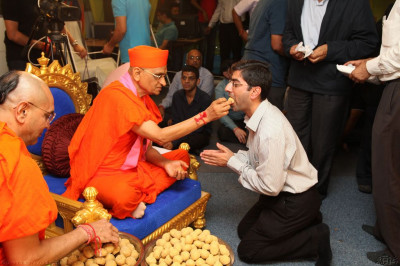 His Divine Holiness Acharya Swamishree presents prasad of a traditional Indian sweet to each disciple