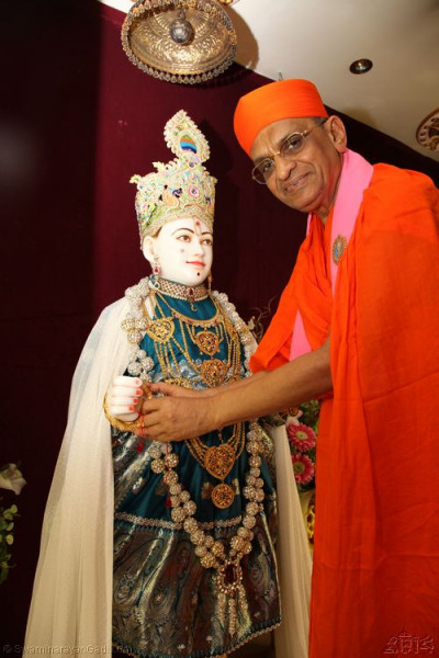 His Divine Holiness Acharya Swamishree offers a large gold Rakhi to Lord Shree Swaminarayan