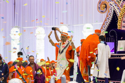 Sants and disciples set off confetti canons as His Divine Holiness Acharya Swamishree reaches the grand front stage