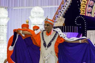 His Divine Holiness Acharya Swamishree holds up the long deep purple robe