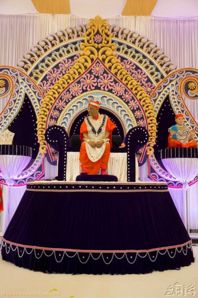 Divine darshan of His Divine Holiness Acharya Swamishree seated within the magnificent stage decorations