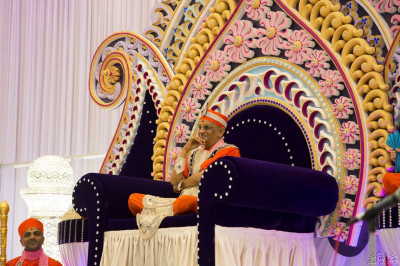Divine darshan of His Divine Holiness Acharya Swamishree seated on His throne set within the magnificent stage decorations