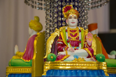 Divine darshan of Lord Shree Swaminarayan, Jeevanpran Shree Abji Bapashree and Jeevanpran Shree Muktajeevan Swamibapa seated within the grand stage decorations