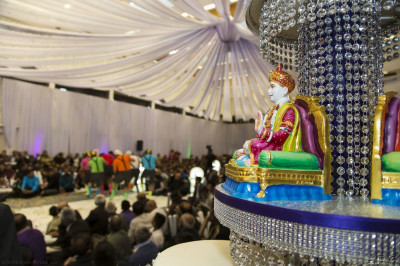 Divine darshan of Lord Shree Swaminarayan seated within the grand stage decorations