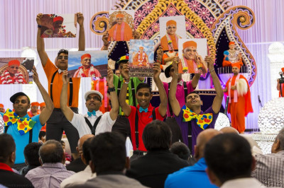 Disciples hold a variety of different photographs of His Divine Holiness Acharya Swamishree over the last 35 years at the conclusion of the dance