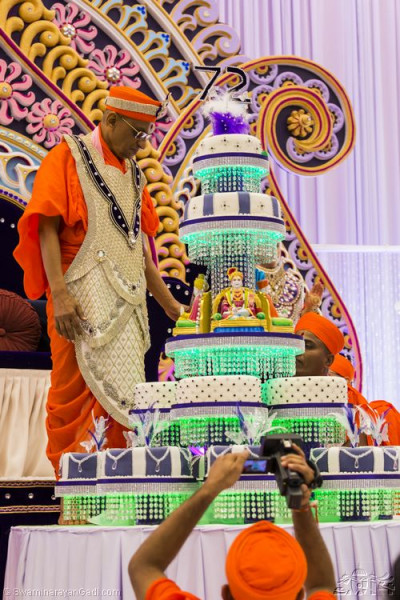 His Divine Holiness Acharya Swamishree stood next to the large cake stand
