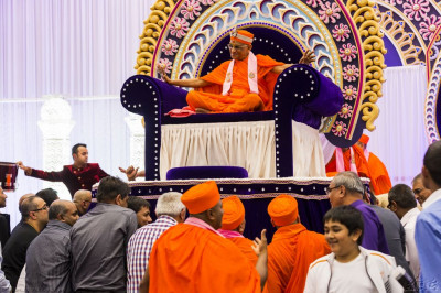 Disciples lift the entire front stage decorations, throne and His Divine Holiness Acharya Swamishree from the front of the hall to the centre