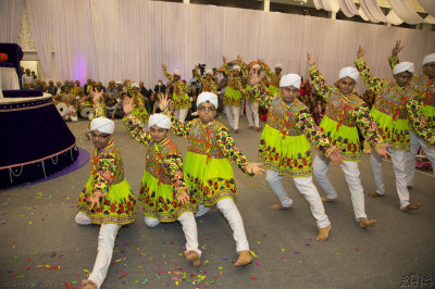 Disicples dressed in white turbans and bright green dress perform a high energy dance