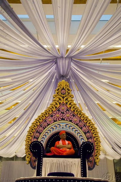 Divine darshan of Acharya Swamishree seated at the centre of Shree Purushottam Mahal with the high ceiling decorations