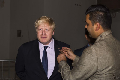 Disciples present the official logo pin of the grand opening festival of Shree Swaminarayan Mandir Kingsbury to Mayor of London Boris Johnson