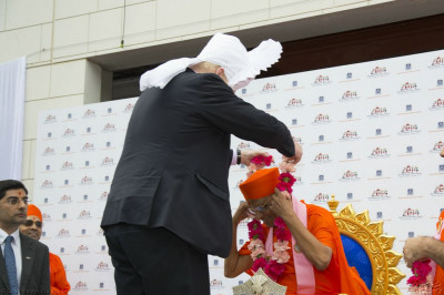 Boris Johnson offers a garland of fresh pink flowers to His Divine Holiness Acharya Swamishree