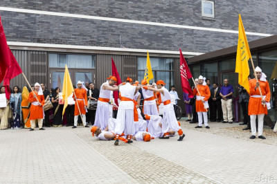 Disciples who are members of Shree Muktajeevan Dance Academy perform a traditional Indian dance with flags outside the entrance of Purushottam Mahal
