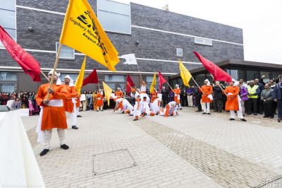 Members of Shree Muktajeevan Dance Academy perform a traditional Indian dance with flags outside the entrance of Purushottam Mahal