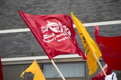 A close up of the red and yellow flags depicting the official 2014 logo of the grand opening of Shree Swaminarayan Mandir Kingsbury